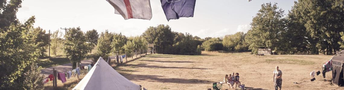 Weißzelt im Lager mit drei wehenden Flaggen